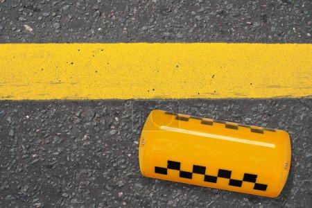 Photo pour Panneau jaune de taxi couché sur la route. Texture, arrière-plan, concept - image libre de droit