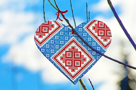Photo pour Coeur fait à la main dans le style de l'ukrainien vyshyvanka sur l'arbre à la main qui enfants faites en raison de la journée de l'Europe à Vinnitsa, Ukraine. Vyshyvanka est le nom familier pour la chemise brodée en costume national ukrainien - image libre de droit