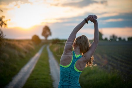 Photo for Happy successful sportswoman raising arms to the sky on golden back lighting sunset summer. Fitness athlete with arms up celebrating goals after sport exercising and working out outdoors. - Royalty Free Image