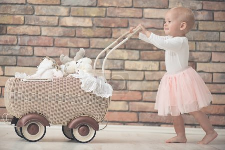 Baby girl with toy baby carriage