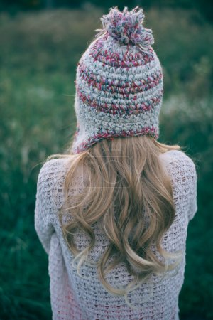 Long hair woman looking away in knitted hat