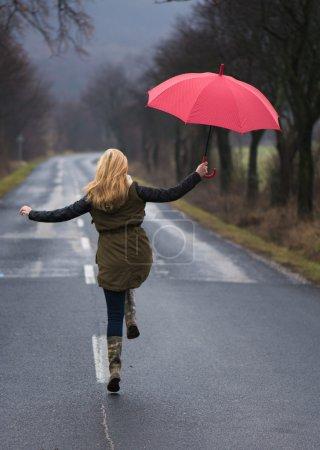 Photo pour Jour de pluie femme tenant parapluie rouge - image libre de droit