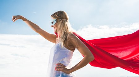 Young woman posing as superhero over blue sky