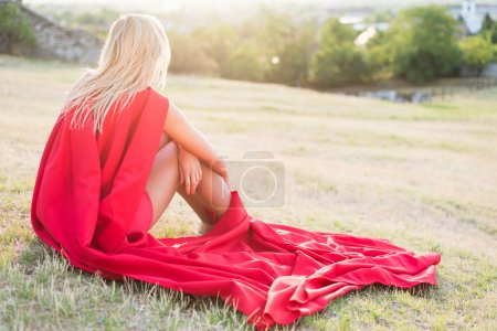 Blonde woman laying in grass outdoor, wearing red dress and looking away