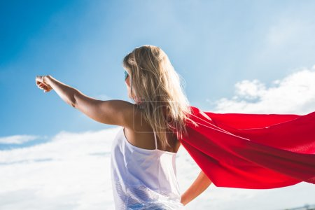 Blonde superhero flying over blue sky and arms up