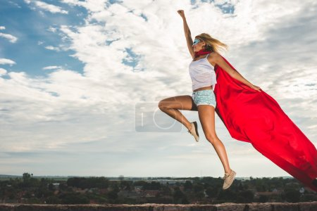 Blonde woman in red dress and red mantle jumping outdoor as a superhero against blue sky