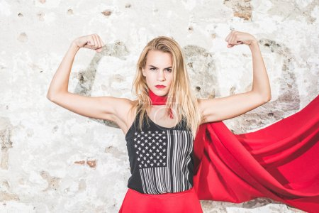 Strong woman posing in front of the camera and shoving biceps