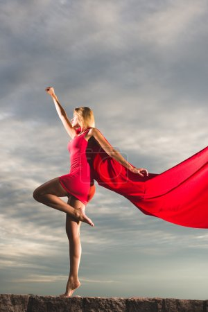 Blonde woman in red dress and red mantle posing outdoor as a superhero against blue sky