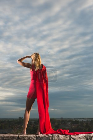 Blonde woman in red costume watching away over the landscape