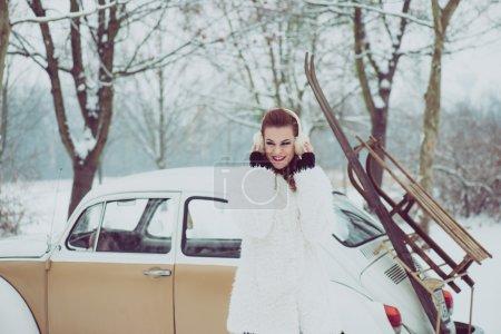 Photo pour Jeune femme posant en plein air avec une voiture vintage, concept de voyage d'hiver rétro - image libre de droit