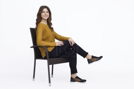 Photo for Happy Young Woman in Sweater And Black Pants Sitting on Chair White Background - Royalty Free Image