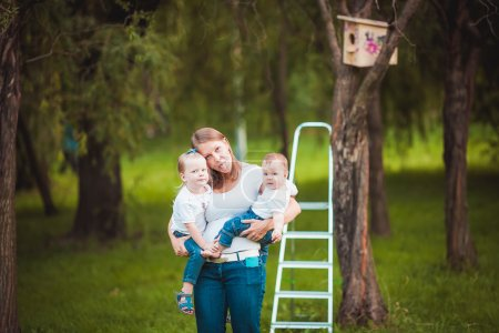 Mother and her daughters with Wooden birdhouse