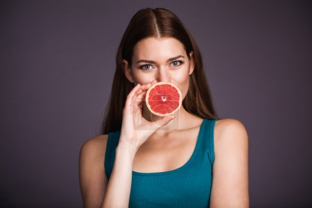 Photo for Young smiling woman holding grapefruit over black background - Royalty Free Image