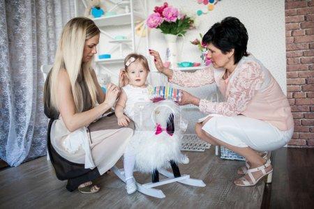 Photo pour Joyeux sourire mère, fille et mamie jouer dans la chambre - image libre de droit