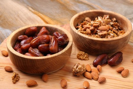 Fruits dates and nuts in wooden bowl  on  table