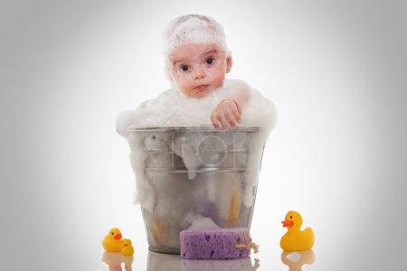 Little baby on a bucket on white background