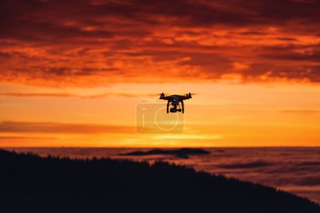 Photo for A personal drone flying through the air, sunrise shot - Royalty Free Image