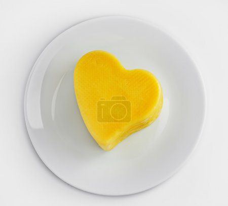 Plate with Cheese in a heart shape isolated on white background