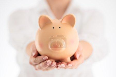 Piggy bank and business concept. Woman holding ceramic piggy ban