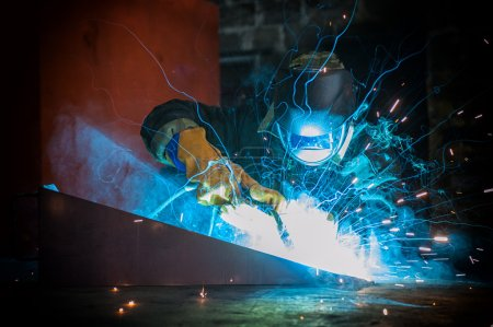 Photo pour Travailleur soudant métal avec étincelles à l'usine - image libre de droit