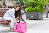 Asian woman looking at shopping bag
