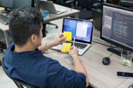 Photo pour Homme d'affaires asiatique avec note collante jaune, vue arrière, pensée, idée, développeur d'ordinateur, travailler au bureau avec ordinateur portable dans le bureau réel - image libre de droit