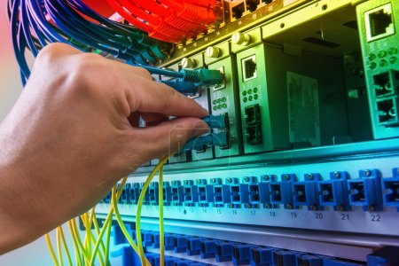 man working in network server room with fiber optic hub for digi