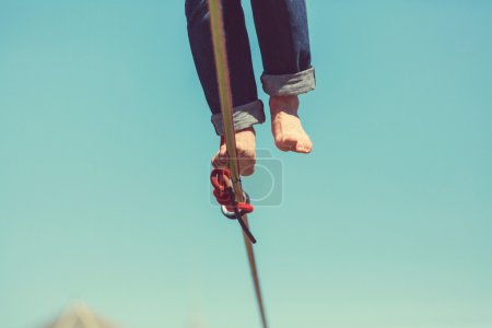 Photo for Slacklining. Sport of balancing on a rope. Close-up human legs. Person practicing in balance. - Royalty Free Image