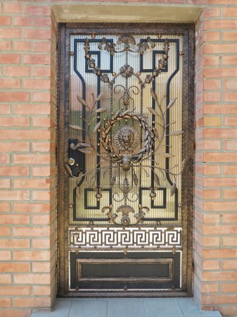 Forged bronze decorative door gate over brick wall background