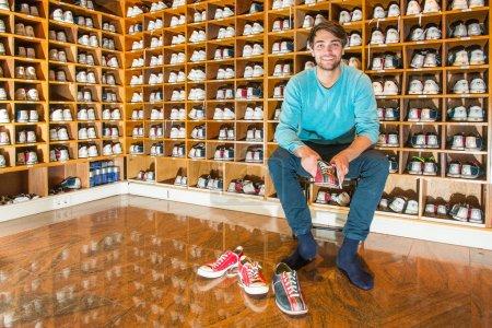 Photo pour Homme, assis sur un tabouret, entouré d'étagères en bois avec différentes tailles de chaussures de bowling, essayant les vêtements de sport, prêt à aller au bowling - image libre de droit