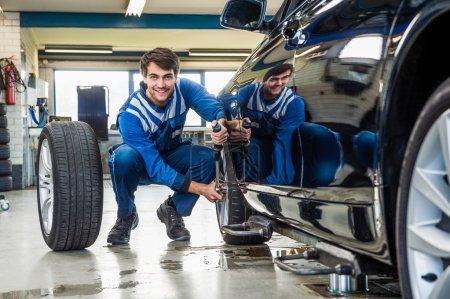 Male mechanic changing car tire