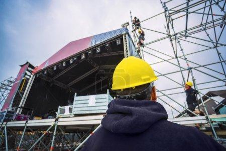 Photo pour Équipe préparant la scène musicale pour un festival, avec un équipement de protection individuelle - image libre de droit