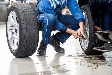 Male mechanic changing car tire