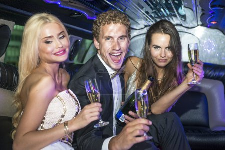 Rich people drinking champagne in a limousine