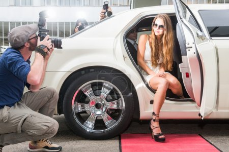 Photo for Female Celebrity Posing In Limousine For Paparazzi On Red Carpet - Royalty Free Image