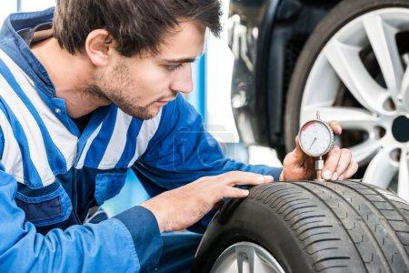 Photo pour Jeune mécanicien mâle pressant la jauge dans la bande de roulement des pneus pour mesurer sa profondeur au garage - image libre de droit