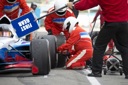 Photo pour Teamwork and professionalism during the skillful tire change at a car race pitstop - image libre de droit