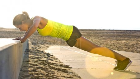 Photo for Young pretty woman doing press ups on a concrete bench at beach, in black sports shorts and neon yellow top - Royalty Free Image