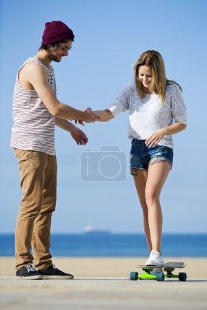 Photo pour Jeune femme, apprenant à faire du skateboard avec son petit ami. Flirtant les uns avec les autres, ils affichent un style de vie et une attitude insouciants, mais dans la rue . - image libre de droit