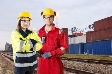 Photo pour Deux gardes de transit de transport ferroviaire en casquettes sur fond industriel - image libre de droit