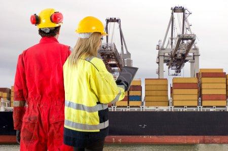 Photo pour Deux dockers en casques avec une tablette électronique sur fond industriel - image libre de droit