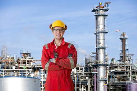Photo pour Opérateur d'usine pétrochimique les bras croisés, posant devant une grande raffinerie pétrochimique - image libre de droit
