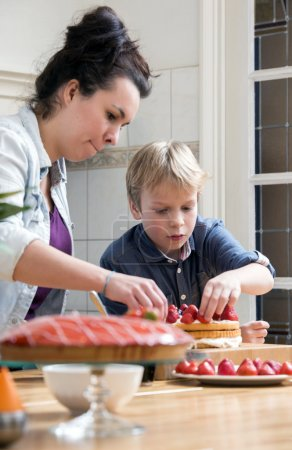 Mother and son topping strawberries