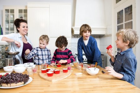 Mother and children decorating cupcakes