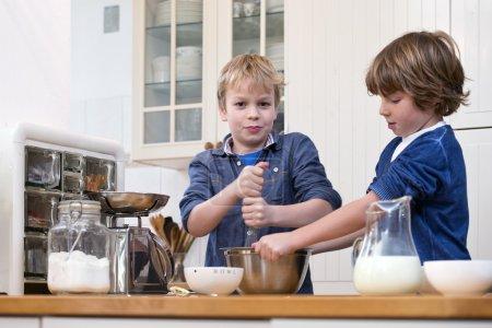 Foto de Dos muchachos batir masa para pasteles en acero inoxidable en la cocina - Imagen libre de derechos