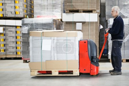 Worker With Loaded Handtruck In Warehouse