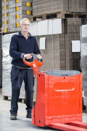 Worker Standing With Handtruck At Warehouse