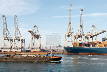 Photo for Large container ships and small coasters are constantly arriving and leaving in a commercial port, being unloaded and loaded with freight - Royalty Free Image