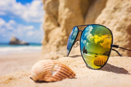 Sunglasses and shell on tropical beach