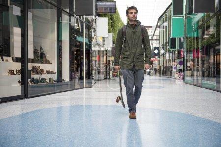Foto de Hombre sosteniendo una tabla de Skate, paseando casualmente más allá de las tiendas en un centro comercial - Imagen libre de derechos